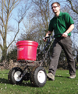 Lawn feed being spread on a lawn. Part of lawn care programme. Tim Hector